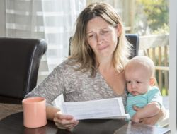 A Mother holding baby and take a look on his bill,